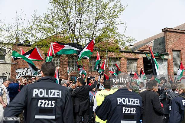 Group of participants of the Palestinians conference on in Berlin, Germany runs with an Oversized Palestinian flag in the direction of the...