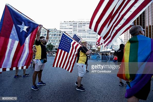 A group of participants wave US and Puerto Rican flags as