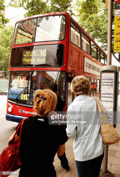 A group of passengers about to board a number 30 doubledecker bus to Marble Arch at a stop outside St Pancras train Station London