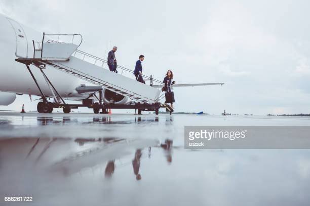 group of passengers disembarking the airplane - leaving stock pictures, royalty-free photos & images