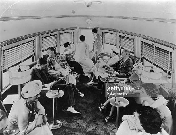 A group of passengers lounge in a train's coneshaped club car appointed with easy chairs lamps and standing ashtrays