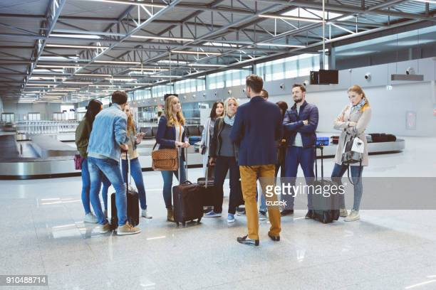 group of passengers standing at airport lounge - izusek stock pictures, royalty-free photos & images