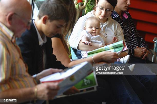 Group of patients including baby, sitting in waiting room of surgery