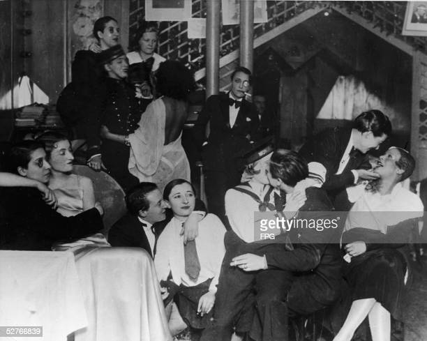 A group of patrons many dressed as men in tuxedos and some with monocles sit talk laugh and kiss at 'Le Monocle' a famous night club for women Paris...