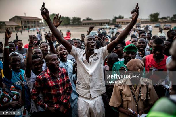 A group of PDP Presidential candidate supporters react while votes for their party are counted at Shagari Primary School polling station in Yola...