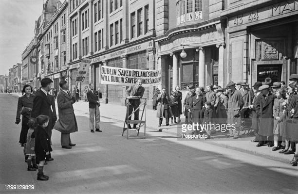 Group of pedestrians and residents gather round to listen to a man speaking at an impromptu Irish language meeting in O'Connell Street, Dublin,...