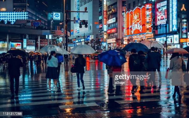 Group of pedestrians crossing street against glowing neon lights and city buildings in downtown Tokyo, Japan on a rainy night