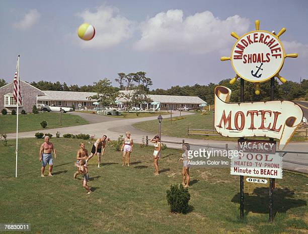 A group of people adults and children all dressed in swimwear play with a beach ball on the grass near the sign for the Hankerchief Shoals Motel Cape...