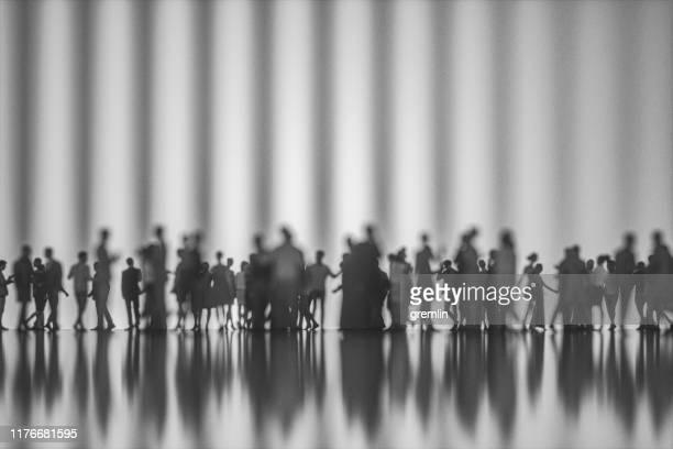 gruppe von menschen gegen moderne glasfassade - mensch im hintergrund stock-fotos und bilder