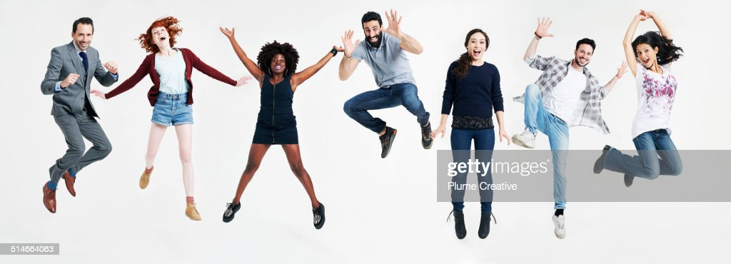 A group of people all jumping up in the air : Stock Photo
