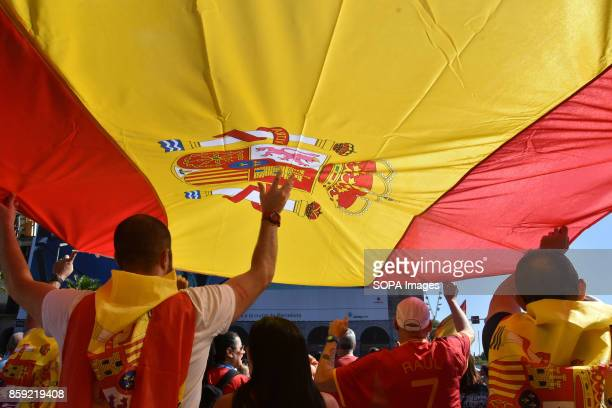 A group of people are pictures holding a huge flag of Spain during the demonstration against the independence of Catalonia Thousands of people...