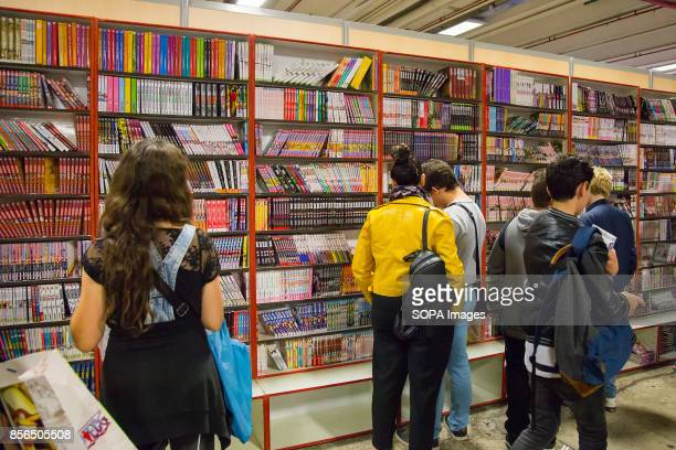 A group of people are pictures while looking at manga books during the 24th edition of the Paris Manga SciFi Show mostly devoted to Japanese...