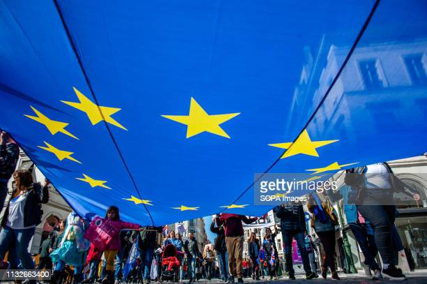 A group of people are seen holding a big flag of the EU during the protest A day before the anniversary of the founding Treaty of the European Union...