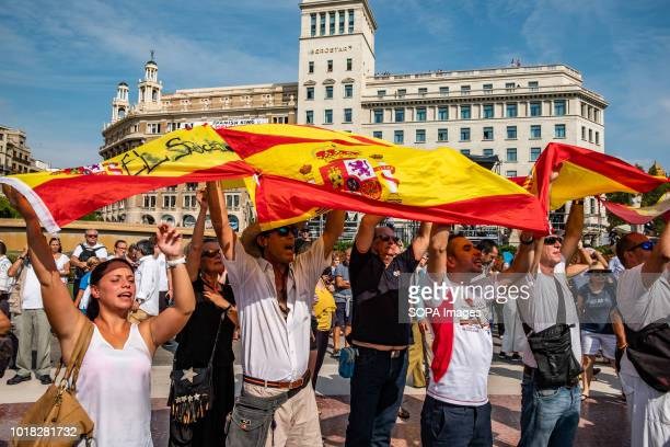 A group of people are seen showing some Spanish flags during the event Barcelona celebrated the first anniversary of the terrorist attack on the...