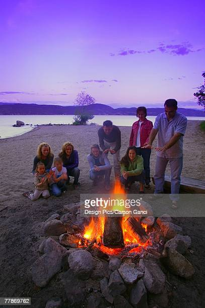 A group of people around a fire on the beach