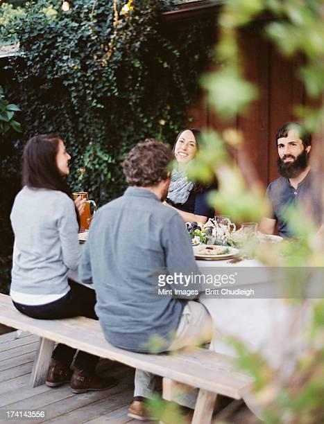 un gruppo di persone attorno a un tavolo in un giardino. una celebrazione - provo foto e immagini stock