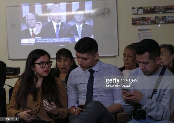 A group of people at a comunity center turn their backs to the screen showing US President Donald Trump delivering his first State of the Union...