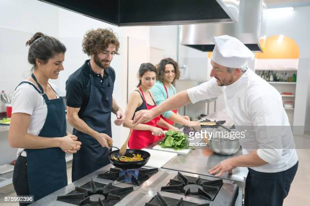 Group of people at a cooking class and chef teaching them how to sauté vegetables on a wok