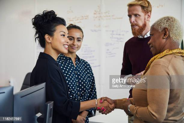 group of people at a start up business having a project meeting - handshake stock pictures, royalty-free photos & images