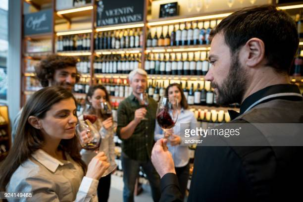 Group of people at a wine tasting in a winery while one woman is smelling the wine with eyes closed