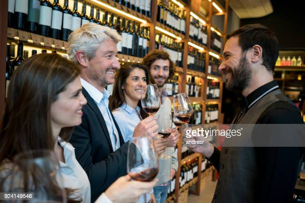 group of people at a winery learning about wine with a friendly sommelier - bar drink establishment stock pictures, royalty-free photos & images