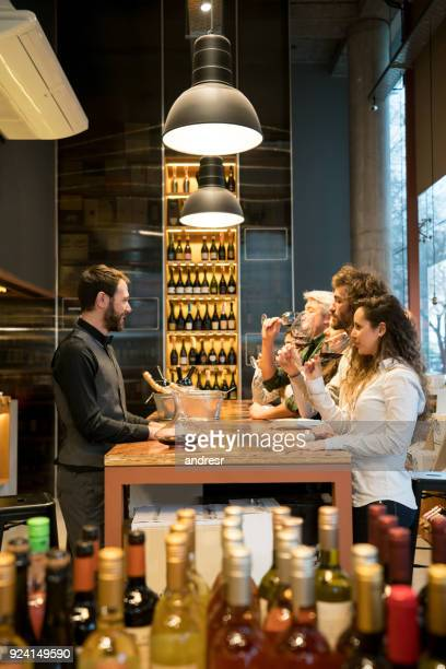 group of people at a winery tasting wines and cheerful sommelier teaching them - bar drink establishment stock photos and pictures