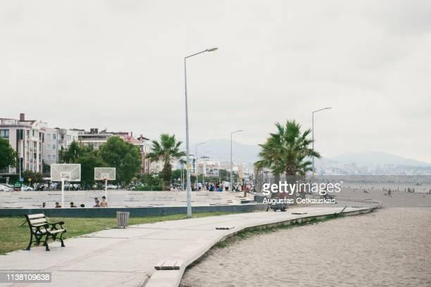 group of people at beach in city against sky - uferpromenade stock-fotos und bilder