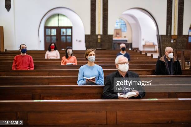 group of people at church congregation during pandemic - kirche stock-fotos und bilder