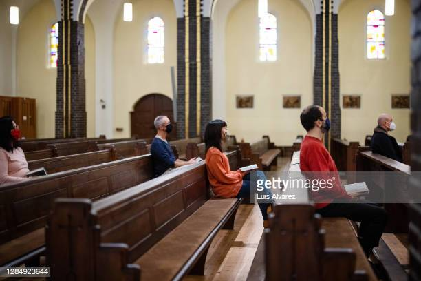 group of people at church congregation wearing face masks. - catholicism stock pictures, royalty-free photos & images