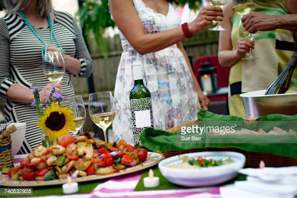 Group of people at garden party, holding wine glasses, making a toast, food on serving plates on table, mid section