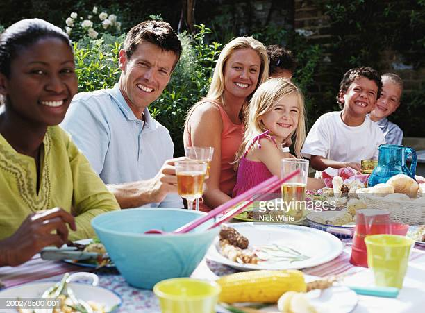 Group of people at lunch table outdoors, smiling, portrait