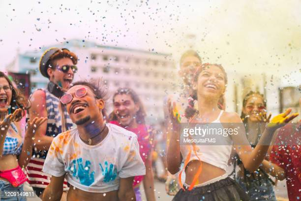 group of people at outdoor color festival - brazilian carnival stock pictures, royalty-free photos & images
