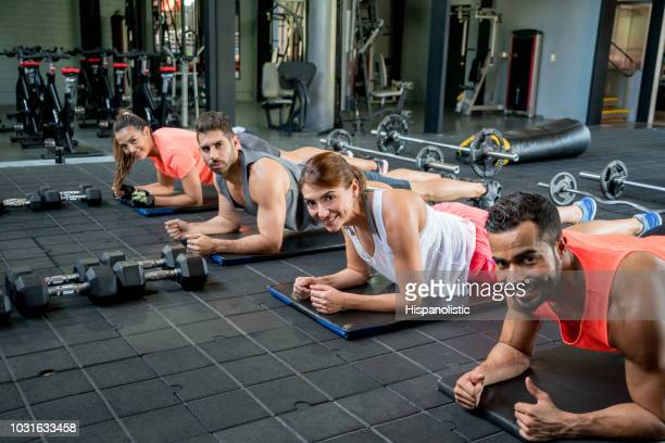 Group of people at the gym training doing planks looking at camera smiling