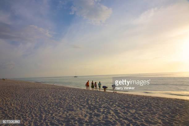 group of people at water's edge stooping looking at shells on captiva beach - captiva island - fotografias e filmes do acervo