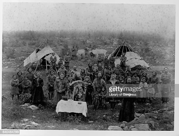 A group of people attend a religious service in Nirchinska Russia in front of two tents Two caribou stand in the rear | Location Nirchinska Russia