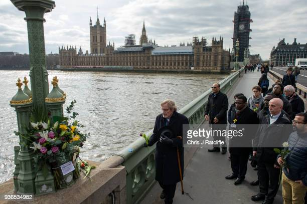 A group of people believed to be staff from St Thomas' Hospital leave flowers at points on Westminster Bridge where victims of the terror attack were...