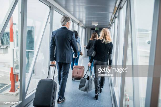 group of people boarding a plane - passenger boarding bridge stock pictures, royalty-free photos & images