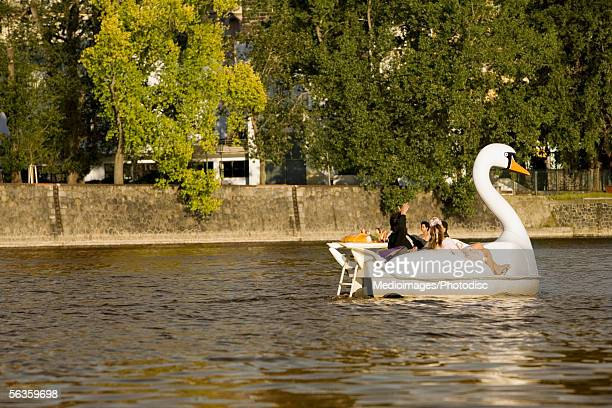 group of people boating in a swan shaped boat, vltava river, prague, czech republic - vltava river stock pictures, royalty-free photos & images