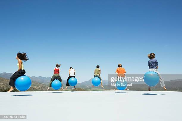 group of people bouncing on inflatable hoppers, on platform, outdoors - hoppity horse stock photos and pictures