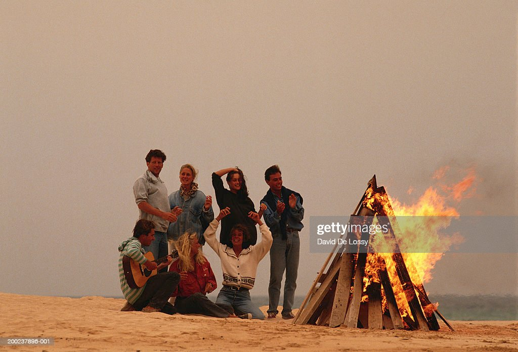 Group of people by campfire at beach : Stock Photo