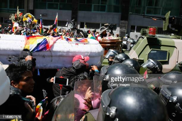 A group of people carrying a coffin attempt to pass throw a police line during a funeral procession for the victims killed during clashes with police...