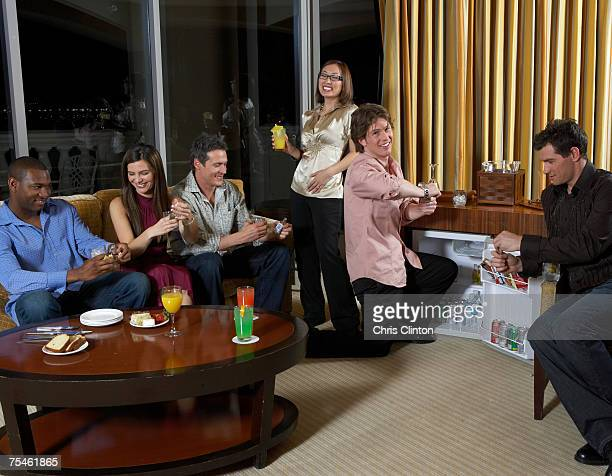 Group of people celebrating in hotel room, having drinks