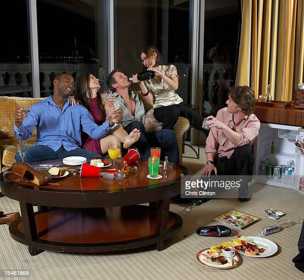 Group of people celebrating in hotel room, woman pouring wine in to man's mouth