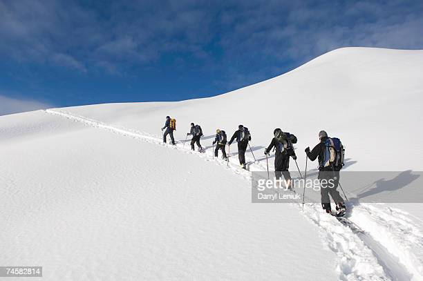 Group of people climbing in snow, low angle view, rear view