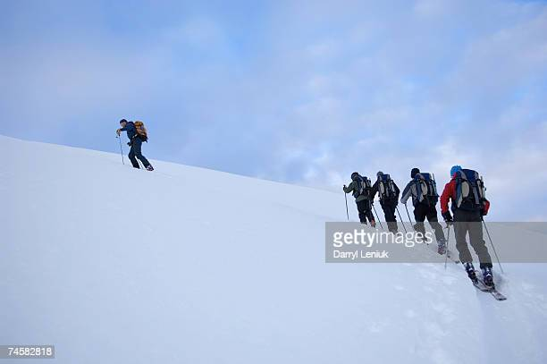 group of people climbing in snow, one leading, low angle view, rear view - sportkleding stock pictures, royalty-free photos & images