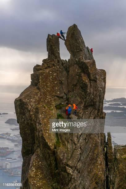 a group of people climbing on the svolvær goat,  150-metre (490 ft), a jagged pinnacle high above the landscape of the lofoten. - felsspitze stock-fotos und bilder