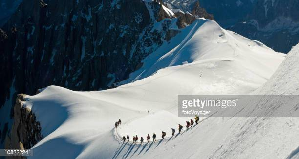group of people climbing snow covered mountain - aiguille de midi stock photos and pictures