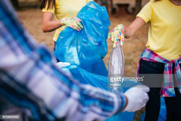 Group of people collects plastic bottles outdoors and packs in a bag