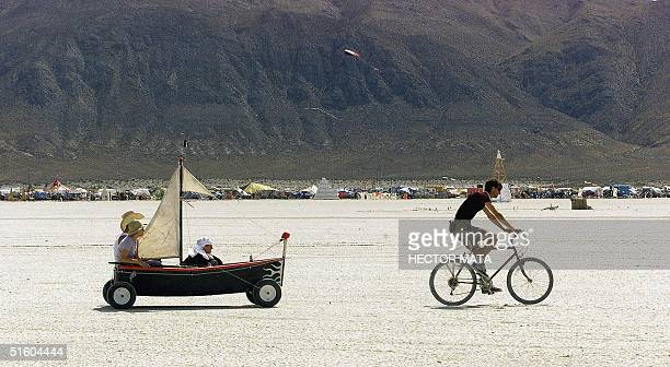 A group of people cross the desert at Black Rock City's Burning Man festival in Nevada 02 September 1999 Founded in 1986 by a group of artists...