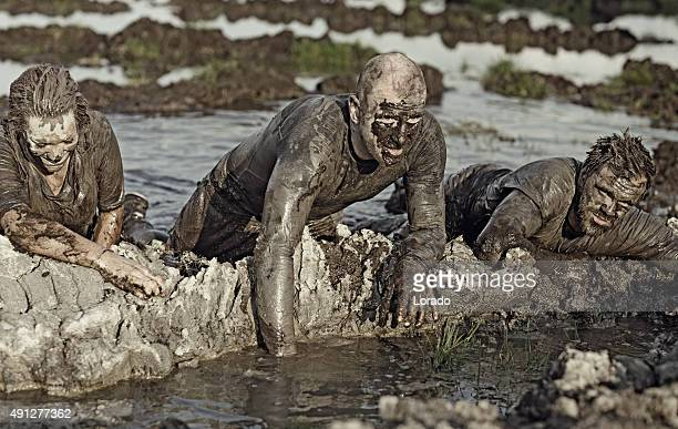 group of people crossing mud obstacle
